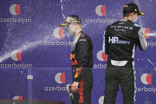 Juri Vips (EST, Hitech Grand Prix), 1st position, and Oscar Piastri (AUS, Prema Racing), 2nd position, spray champagne on the podium