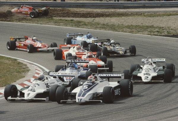 Alan Jones, Williams FW07D Ford, alongside Nelson Piquet, Brabham BT49C Ford as Gilles Villeneuve, Ferrari 126CK, spins off at the start.