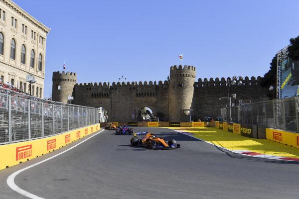 Lando Norris, McLaren MCL34, leads Daniil Kvyat, Toro Rosso STR14, and Carlos Sainz Jr., McLaren MCL34