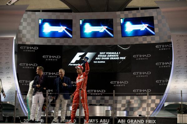 Yas Marina Circuit, Abu Dhabi, United Arab Emirates. Sunday 26 November 2017. Davis Coulthard, Channel 4 F1, Martin Brundle, Sky Sports F1, and Sebastian Vettel, Ferrari, 3rd Position, on the podium. World Copyright: Glenn Dunbar/LAT Images  ref: Digital Image _31I9370