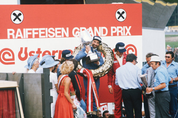 Osterreichring, Zeltweg, Austria. 13-15 August 1976.  John Watson (Penske PC4-Ford), 1st position, celebrates taking his maiden Grand Prix win and Penske's only victory with Jacques Laffite (Ligier JS5-Matra), 2nd position and Gunnar Nilsson (Lotus 77-Ford), 3rd position on the podium, portrait.  World Copyright: LAT Photographic . Ref: 76 AUT 03.