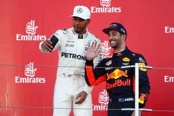 Suzuka Circuit, Japan. Sunday 8 October 2017. Lewis Hamilton, Mercedes AMG, 1st Position, and Daniel Ricciardo, Red Bull Racing, 3rd Position, take a photo on the podium. World Copyright: Andrew Hone/LAT Images  ref: Digital Image _ONY8902