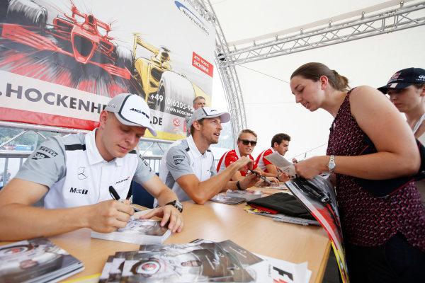 Hockenheimring, Hockenheim, Germany. Saturday 19 July 2014. Kevin Magnussen, McLaren, and Jenson Button, McLaren, sign autographs for fans. World Copyright: Charles Coates/LAT Photographic. ref: Digital Image _N7T4197