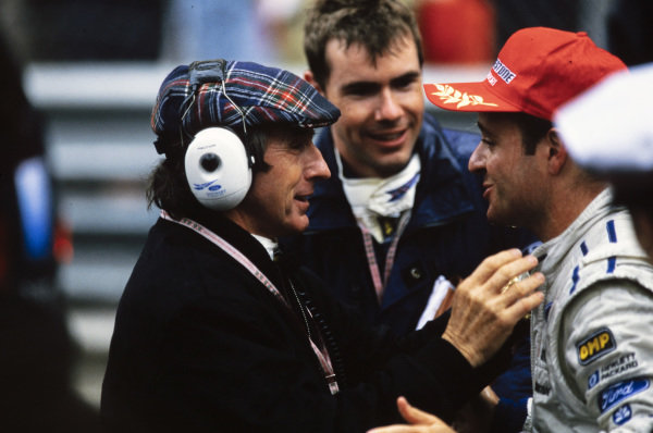 Jackie Stewart and Paul Stewart congratulates Rubens Barrichello on his second-placed finish, giving the Stewart Grand Prix team its first podium finish.