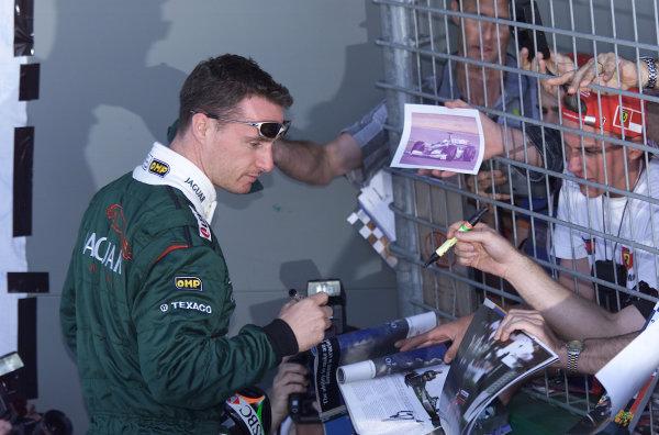 2000 Australian Grand Prix.Albert Park, Melbourne, Australia.10-12 March 2000.Eddie Irvine (Jaguar) signs some autographs for the fans.ref:18mb digitalWorld Copyright - Steve Etherington/EPI