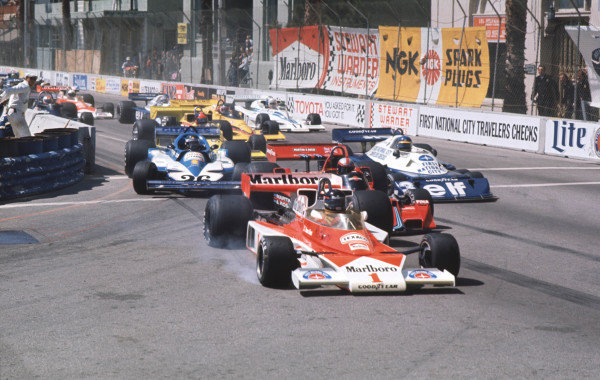 1977 United States Grand Prix West.Long Beach, California, USA.1-3 April 1977.James Hunt (McLaren M23 Ford) locks up and takes off over the front wheel of John Watson's Brabham BT45B Alfa Romeo, in the chain reaction of collisions at Cooks Corner on the first lap.World Copyright - LAT Photographic