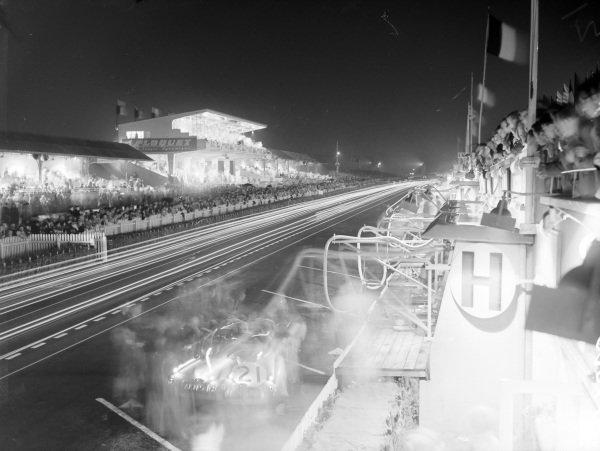 Light trails along the pit straight at night, as Robert Lawrie / Ivan Waller, Jaguar XK-120, make a pitstop.