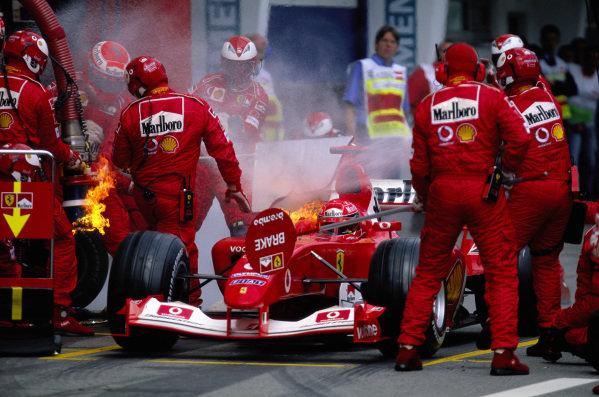 Michael Schumacher's Ferrari F2003-GA, catching fire during a pitstop.