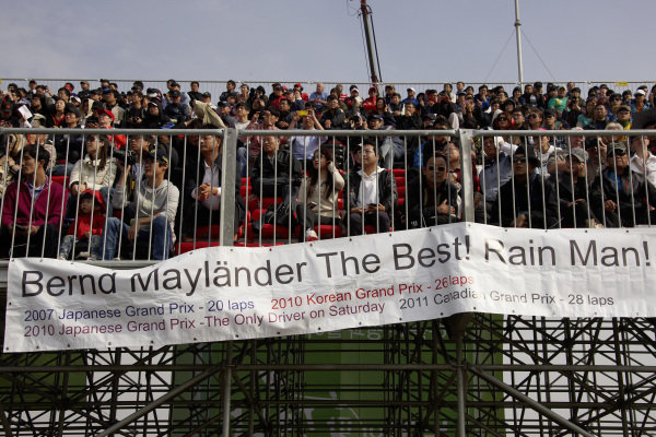Bernd Mayländer's fans in the grandstand, with a banner pointing out some of his longest stints in grand prix racing.