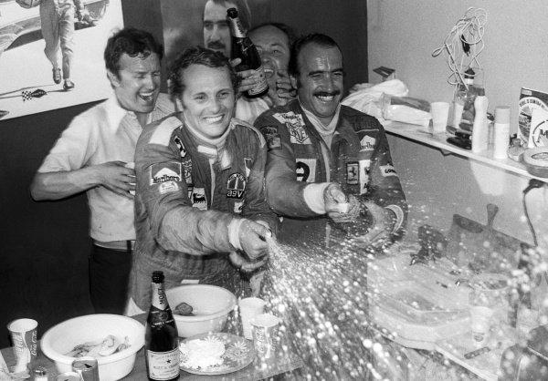 (L to R): New World Champion Niki Lauda (AUT) celebrates with race winner and Ferrari team mate Clay Regazzoni (SUI) in the Ferrari hospitality area. Italian Grand Prix, Rd 13, Monza, Italy, 7 September 1975.