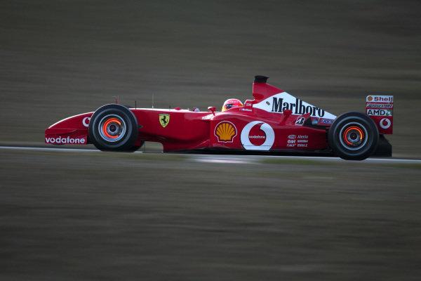 Michael Schumacher drives the new Ferrari F2002, with brake discs glowing.