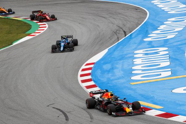 Sergio Perez, Red Bull Racing RB16B, leads Esteban Ocon, Alpine A521, Carlos Sainz, Ferrari SF21, and Lando Norris, McLaren MCL35M