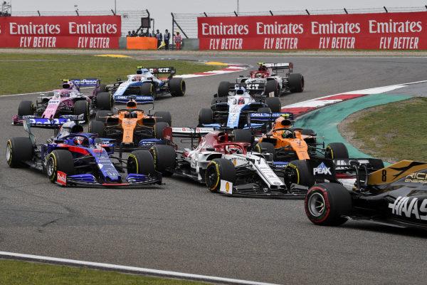 Romain Grosjean, Haas VF-19, leads Kimi Raikkonen, Alfa Romeo Racing C38, Daniil Kvyat, Toro Rosso STR14, Lando Norris, McLaren MCL34, Carlos Sainz Jr., McLaren MCL34, George Russell, Williams Racing FW42, and the remainder of the field at the start