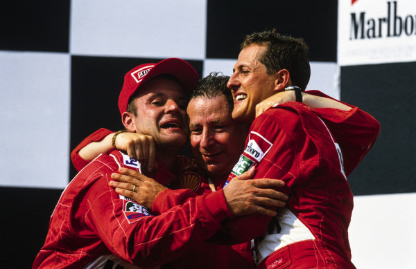 Jean Todt celebrates clinching both the constructors' and drivers' world championships on the podium with Rubens Barrichello, 2nd position, and Michael Schumacher, 1st position.
