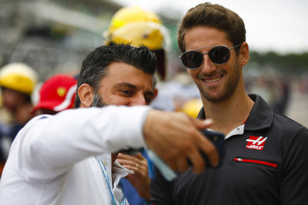 Romain Grosjean, Haas F1 Team, poses for a picture with a fan.