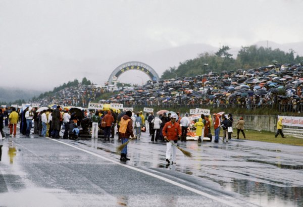Two track officials at the front of the grid use brushes in a desperate attempt to sweep some of the surface water from the track surface. The inaugural Japanese GP was nearly cancelled before being run at the last possible moment in terrible conditions.