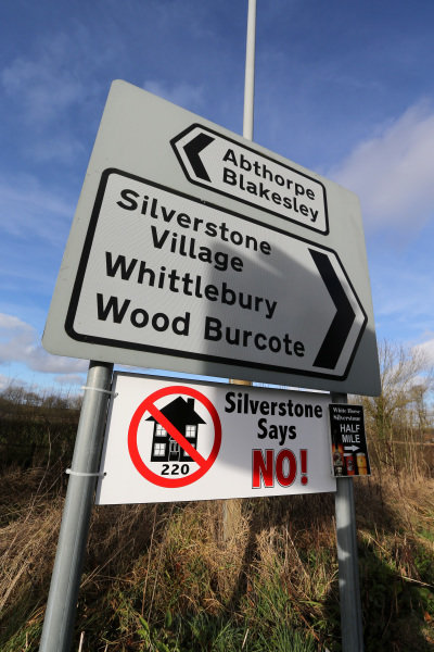 A road sign with a protest banner saying 'Silverstone Says No!' to 220 new houses planned for the village. Jordan Technology Park, Silverstone, England, 1 February 2013.