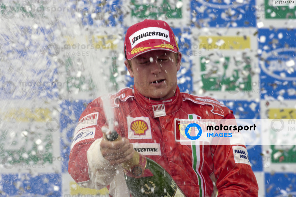 Kimi Räikkonen celebrates race and championship victory on the podium with a champagne shower.