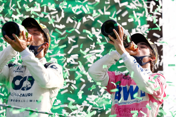Pierre Gasly, AlphaTauri, 1st position, and Lance Stroll, Racing Point, 3rd position, celebrate on the podium with Champagne