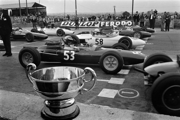 Cars on the grid for the start. Mike Spence, Lotus 32 Ford, Frank Gardner, Brabham BT10 Ford, and Jackie Stewart, Lotus 32 Ford, make up the front row. The champion's trophy is in the front of frame.
