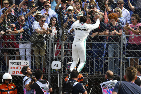 Lewis Hamilton, Mercedes AMG F1, climbs a fence after taking pole position