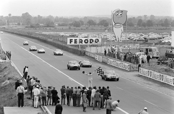 Gerald Langlois van Ophem / Jean Blaton, Ecurie Nationale Belge, Ferrari 250GTO, leads Peter Bolton / Ninian Sanderson, AC Cars, AC Cobra-Ford, Michael Parkes / Umberto Maglioli, Scuderia Ferrari, Ferrari 250P, and others towards the finish line and chequered flag.
