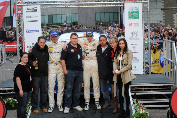 Craig Breen (IRL) and Paul Nagle (IRL), Ford Fiesta S2000, with the family of Gareth Roberts (GBR) on the podium.