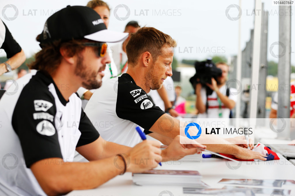 Hungaroring, Budapest, Hungary. Thursday 23 July 2015. Jenson Button, McLaren, and Fernando Alonso, McLaren, sign autographs for fans. World Copyright: Charles Coates/LAT Photographic ref: Digital Image _J5R0859