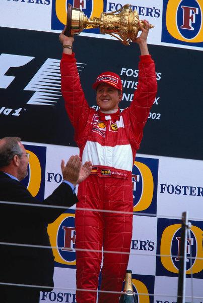 2002 British Grand Prix, Silverstone, England. 7th July 2002. Michael Schumacher, Winner of the British Grand Prix holds the trophy high.World Copyright - LAT Photographic Ref: 35mm Original A04
