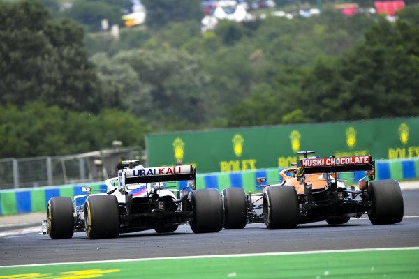 Daniel Ricciardo, McLaren MCL35M, passes Mick Schumacher, Haas VF-21