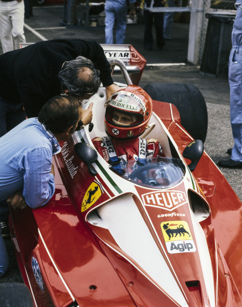 Niki Lauda talks to team members whilst sat in his Ferrari 312T2.