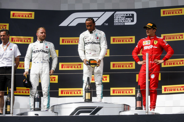 Valtteri Bottas, Mercedes AMG F1, 2nd position, Lewis Hamilton, Mercedes AMG F1, 1st position, and Charles Leclerc, Ferrari, 3rd position, stand for the national anthems on the podium