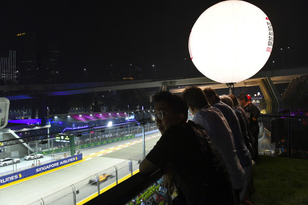 Fans watch from a balcony as Lando Norris, McLaren MCL34, passes