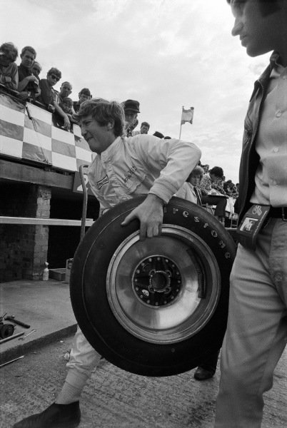 Jochen Rindt carries a Firestone tyre through the pits.