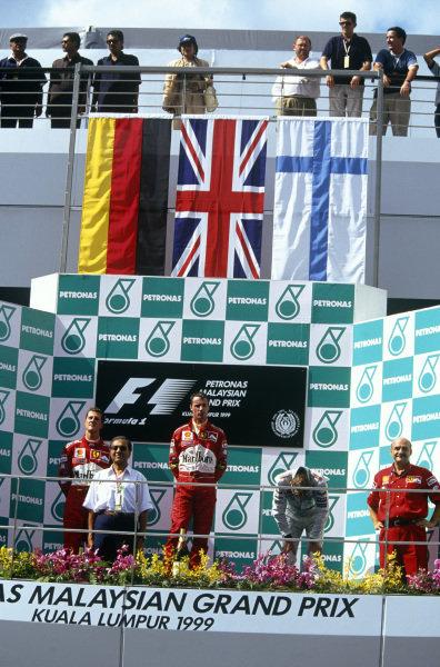 Sepang, Kuala Lumpur, Malaysia. 15-17 October 1999. Eddie Irvine (Ferrari) 1st position, Michael Schumacher (Ferrari) 2nd position and an exhausted Mika Hakkinen (McLaren Mercedes) 3rd position on the podium. Ref: 99MAL19. World Copyright - LAT Photographic