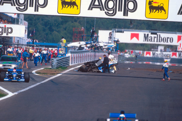 Estoril, Portugal.22-24 September 1995.Luca Badoer nervously walks over to the upside down wreckage of Ukyo Katayama's Tyrrell 023 Yamaha. Katayama went through a number of horrifying somersaults after interlocking wheels with Badoer at the start. He was uninjured in the incident.Ref-95 POR 10.World Copyright - LAT Photographic