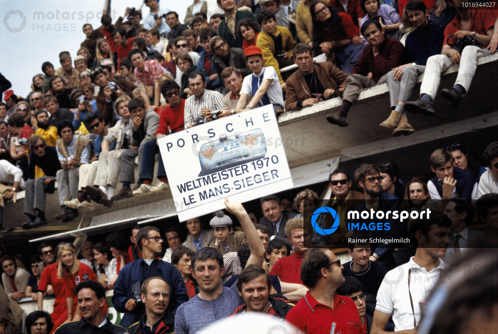 Race spectators hold up a banner to show their support for the Porsche teams.
