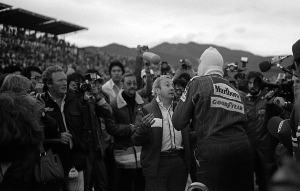 Teddy Mayer (USA), McLaren Team Manager, centre, chats to James Hunt (GBR), climbing out of his McLaren immediately after the race, to signal that he had finished the race in third place and that he was now the 1976 Formula One World Champion. Hunt, who needed to finish fourth or higher to take the title, had climbed out of the car angry and unaware of his situation after a late race puncture had dropped him to fifth place.  Japanese Grand Prix, Rd16, Fuji, Japan, 24 October 1976.