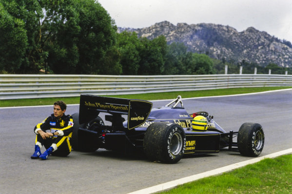 Ayrton Senna, sits down beside his Lotus 97T Renault. His helmet is on the side of the car.