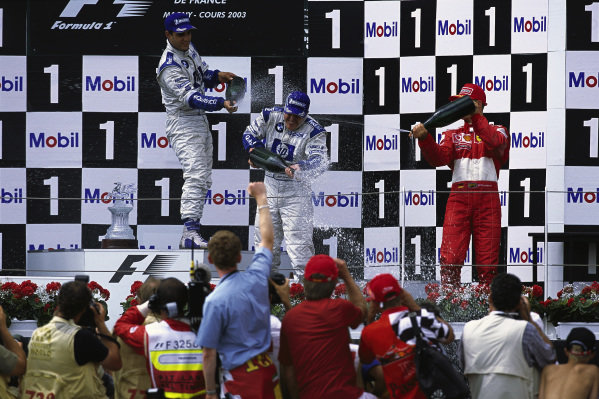 Ralf Schumacher, 1st position, Juan Pablo Montoya, 2nd position, and Michael Schumacher, 3rd position, celebrate on the podium.