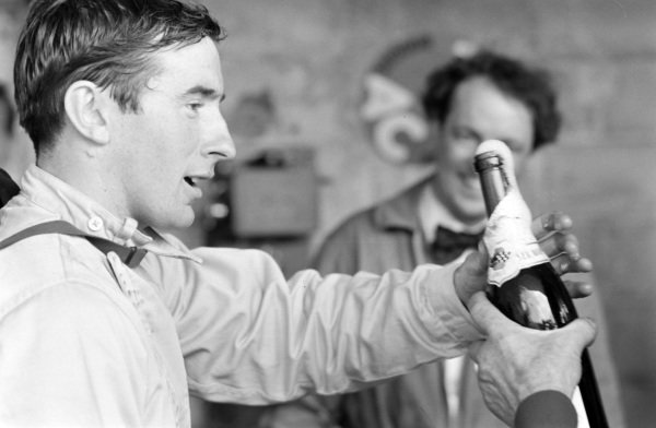 Jackie Stewart is handled a bottle of champagne.