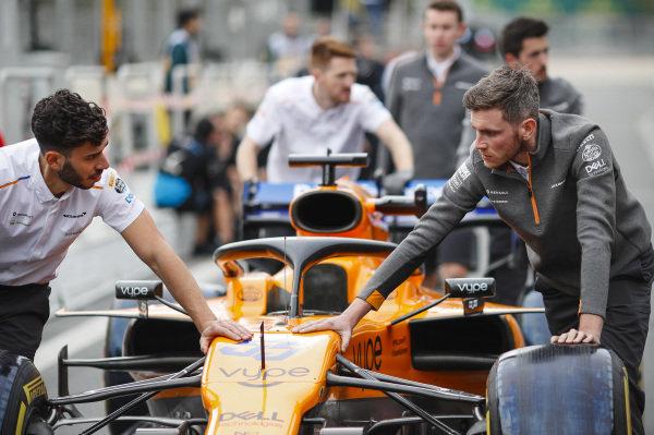 McLaren engineer pushes car of Carlos Sainz Jr., McLaren MCL34 down the pit lane