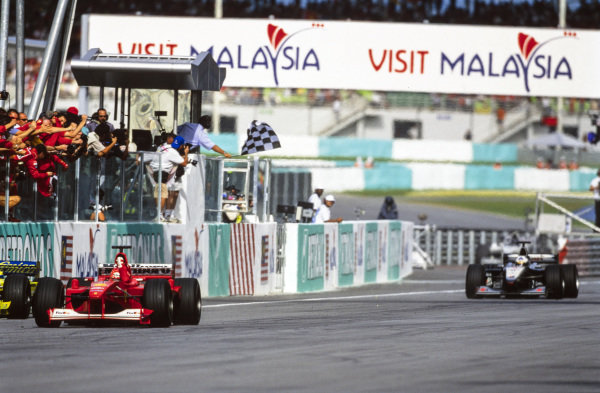 Michael Schumacher, Ferrari F1-2000, leads David Coulthard, McLaren MP4-15 Mercedes, as they take the chequered flag.