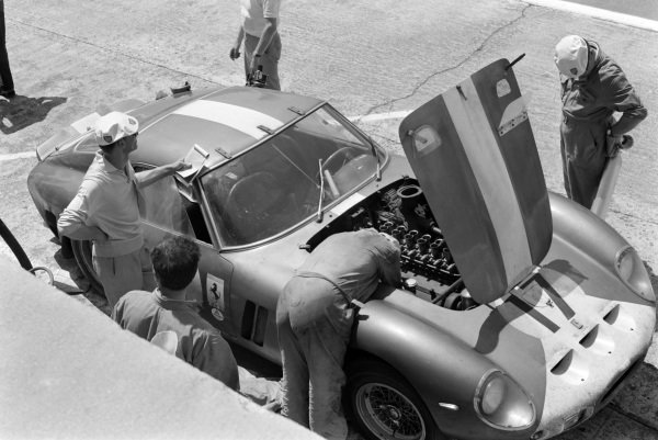 A mechanic works on the engine in Bob Grossman / Glenn Roberts' North American Racing Team, Ferrari 250 GTO, during a pitstop.