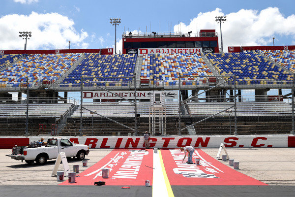 Track workers paint logos on the front stretch.  Copyright: Chris Graythen / Getty Images