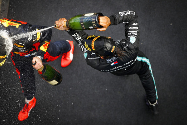 Lewis Hamilton, Mercedes-AMG Petronas F1, 1st position, and Max Verstappen, Red Bull Racing, 2nd position, celebrate on the podium with Champagne