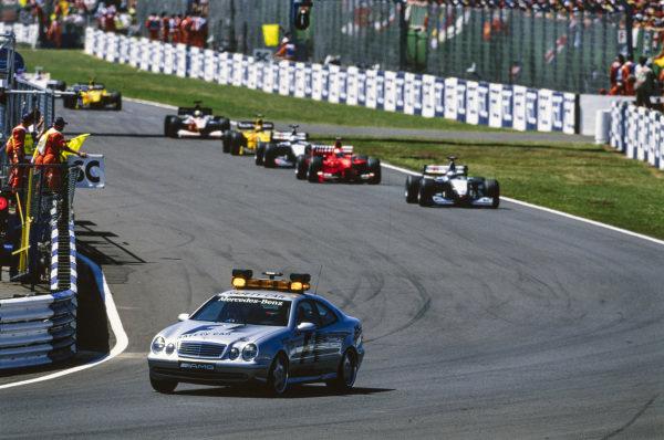 The Safety Car leads Mika Häkkinen, McLaren MP4-14 Mercedes, Eddie Irvine, Ferrari F399, David Coulthard, McLaren MP4-14 Mercedes, Heinz-Harald Frentzen, Jordan 199 Mugen-Honda, Ralf Schumacher, Williams FW21 Supertec, and Damon Hill, Jordan 199 Mugen-Honda.