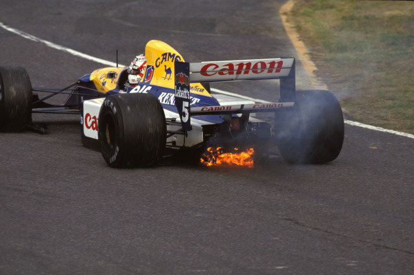 Smoke and flames pour from the back of Nigel Mansell's Williams FW14B Renault.
