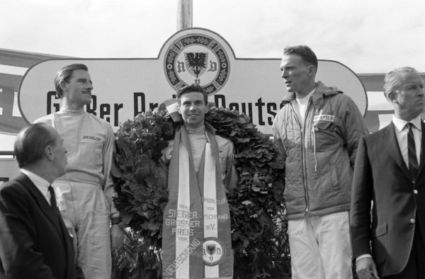 Race winner Jim Clark on the podium with Graham Hill, 2nd position, and Dan Gurney, 3rd position.