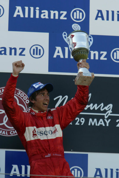 2004 Formula 3000 Championship (F3000) Nurburgring, Germany.29th May 2004. Enrico Toccacelo (BCN F3000) shows off his winner's trophy on the podium.World Copyright: LAT Photographic ref: Digital Image Only